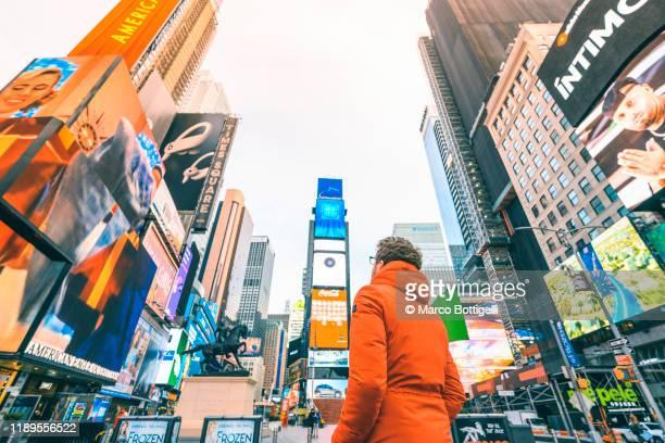 tourist admiring times square, new york city - マンハッタン タイムズスクエア ストックフォトと画像