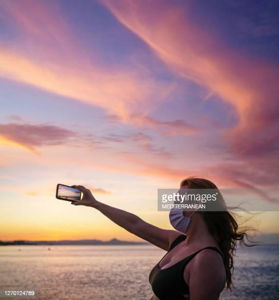 turista adulto de los años 50 mujer en pandemia máscara de la cara en la playa del atardecer tomando fotos - vista marina fotografías e imágenes de stock