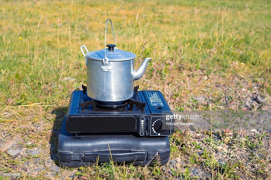 Tourist aluminum kettle on a gas stove : Foto de stock