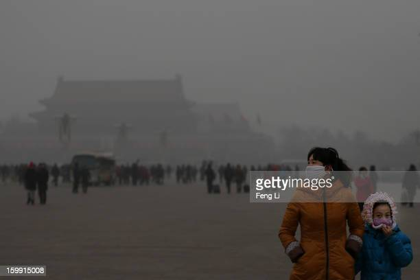 A tourist and her daughter wearing the masks visit the Tiananmen Square at dangerous levels of air pollution on January 23 2013 in Beijing China The...