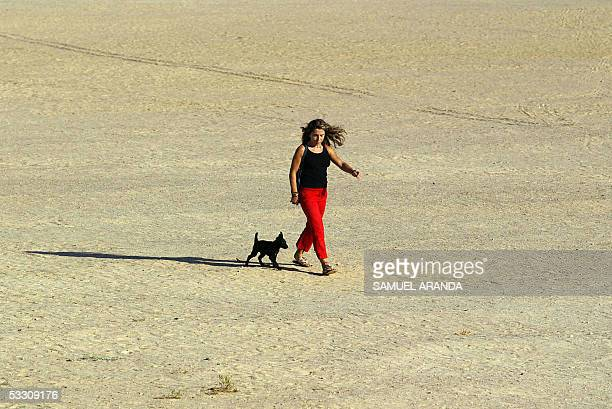 A tourist and her dog walk on a beach in the touristic area of El Castillo 31 July 2005 on the Canary Islands Thousands of tourists most of them from...