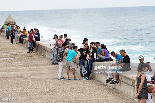 Tourist and locals sitting by The Malecon sea wall looking out to the beautiful blue ocean