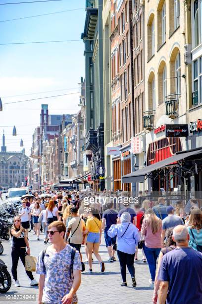 Tourist and shopping crowd on the Damrak street in Amsterdam during Summer