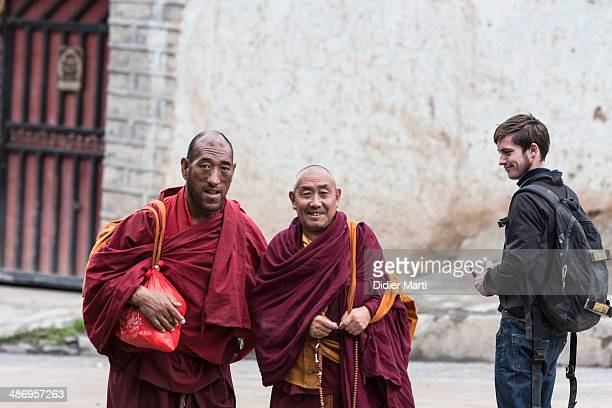 Tourist and two monks in Ganzi in Sichuan in China