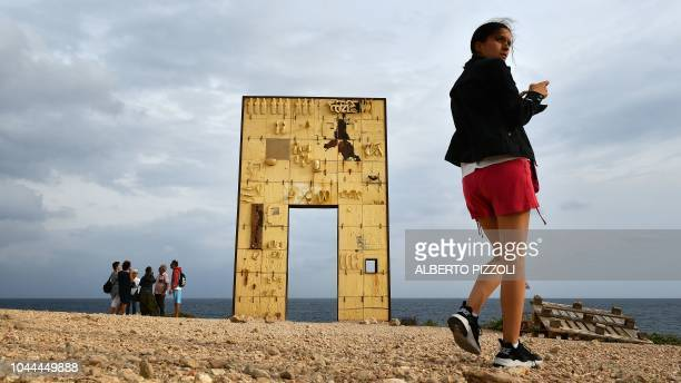Tourist are pictured by the Porta di Lampedusa known as The door of Europe a monument to the migrants who have died in the Mediterranean located at...