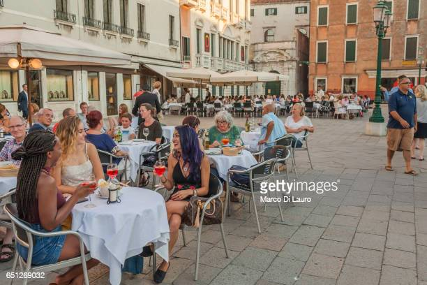 Tourist are seen sitting in a Cafe in Campo Santo Stefano on June 30 2015 in Venice Italy According to UNESCO Venice is in clear and urgent need of a...
