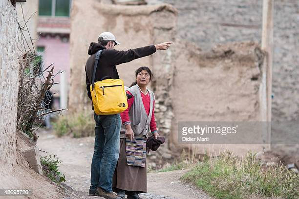 Tourist asking for direction to a local woman in Ganzi in Sichuan province of China