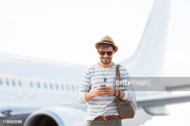 tourist am flughafen mit telefon - izusek stock-fotos und bilder