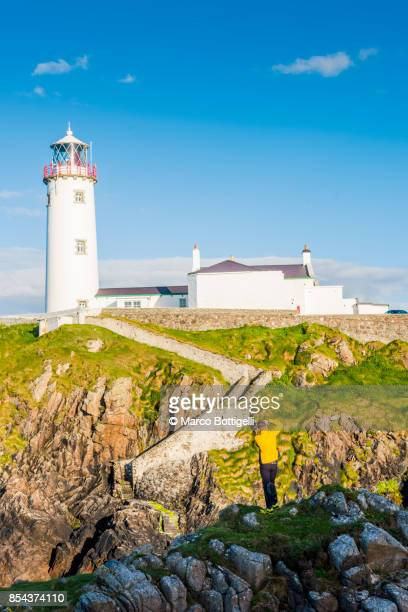 tourist at fanad head lighthouse, donegal, ireland. - county donegal stock photos and pictures