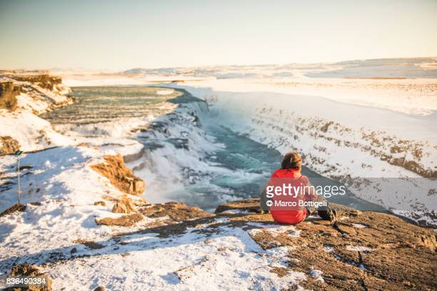 Tourist at Gullfoss waterfall, Iceland.