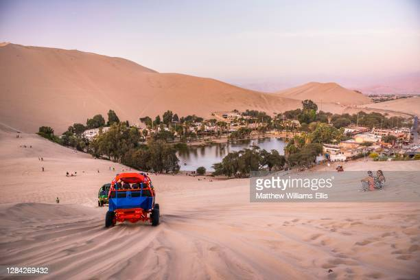 Tourist at Huacachina at sunset in the desert in the Ica Region, Peru, South America.