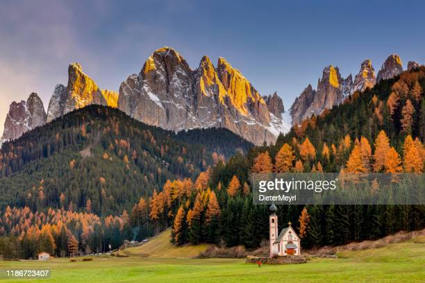 tourist at san giovanni church in front of odle group, trentino alto adige region, italy - unesco stock pictures, royalty-free photos & images