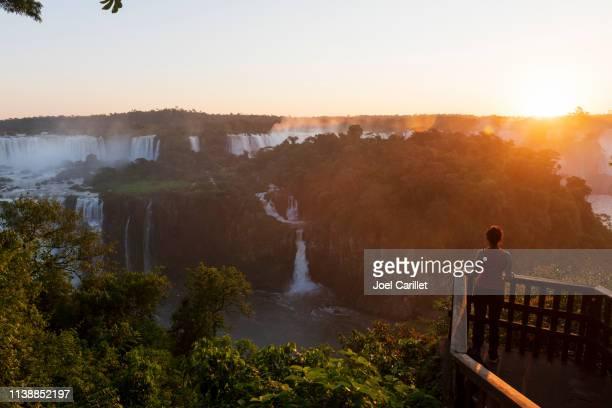 tourist at sunset at iguazu falls, brazil - iguacu falls stock pictures, royalty-free photos & images