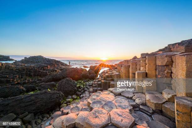 tourist at sunset over giants causeway, northern ireland - coastline stock photos and pictures