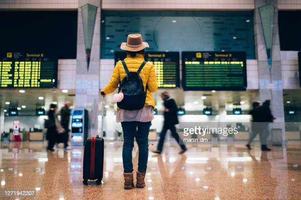 toerist bij de luchthaven die de aankomstraad controleert - toerisme stockfoto's en -beelden