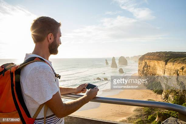 Tourist at the Twelve Apostles using mobile phone-Australia