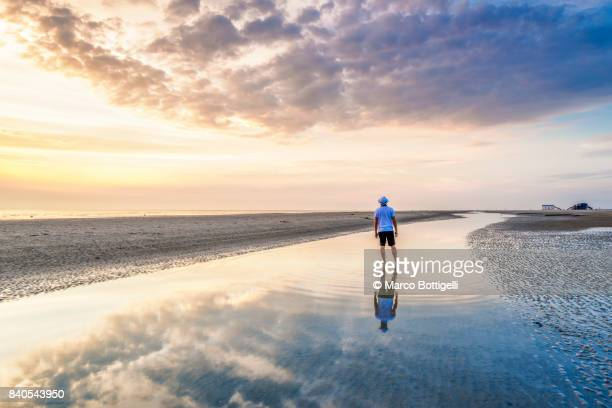 Tourist at the Wadden Sea at sunset. St. Peter-Ording, Germany.