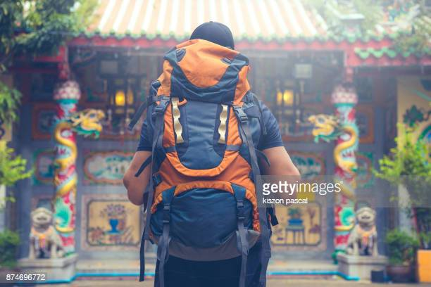 tourist backpacker visiting a temple in southeast asia . .