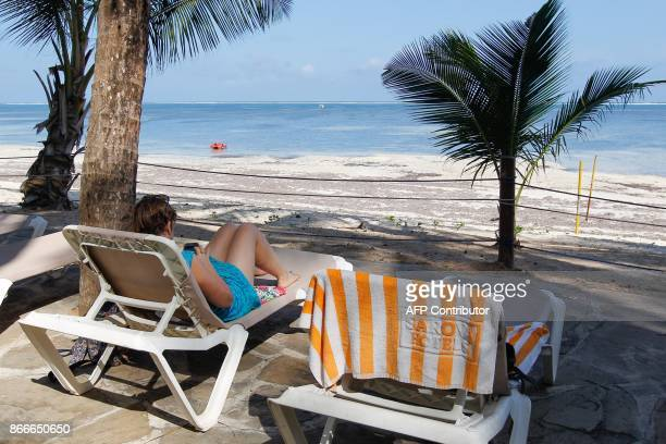A tourist bathes in the sun on a beach in Mombasa souhern Kenya on October 26 2017 during the country's rerun presidential election At least three...