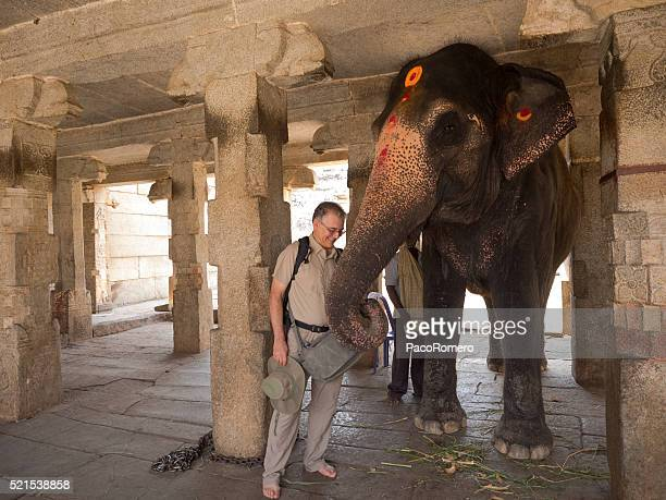 Tourist being blessed by Indian elephant in Virupaksha Temple, Hampi