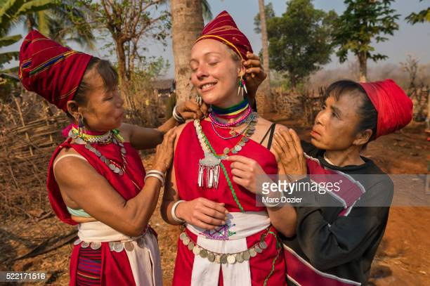 Tourist being dressed by Kayah women