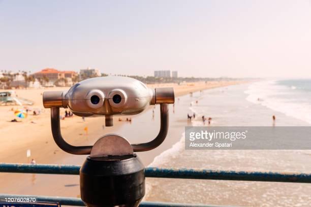 tourist binoculars overlooking santa monica beach, los angeles, california, usa - la waterfront stock pictures, royalty-free photos & images