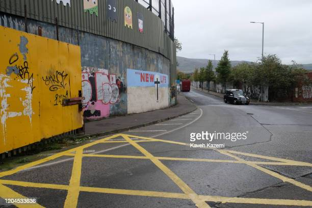 A tourist black cabbie drives near the entrance of the peace line with a mural showing a Cross with written words promising a u201cNEW LIFEu201d...