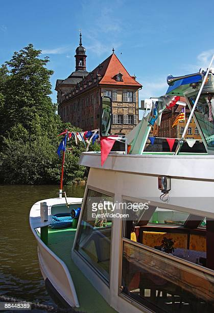 A tourist boat and the former City Hall at the river Regnitz with its facade in rococo style on June 11 2009 in Bamberg Germany Bamberg is listed as...