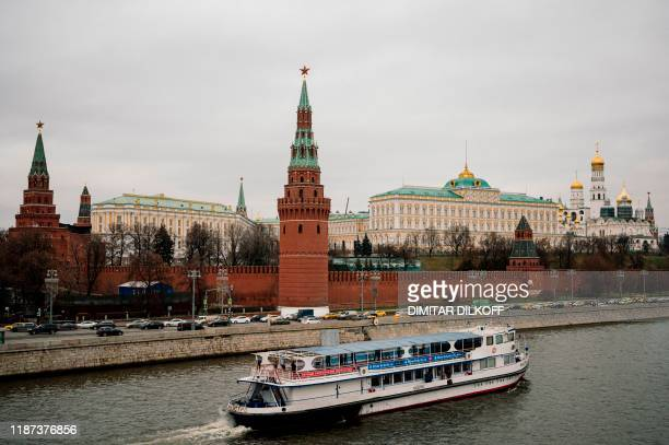 Tourist boat floats on the Moskva river in front of the Kremlin in downtown Moscow on December 9, 2019. - Russia will miss next year's Tokyo Olympics...