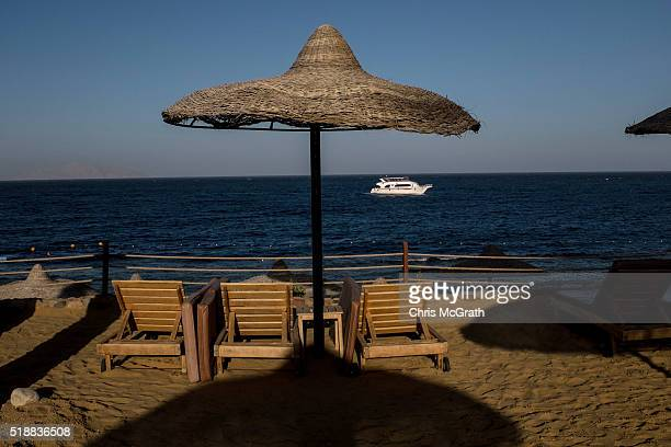Tourist boat is seen passing by empty beach chairs at a resort on March 31, 2016 in Sharm El Sheikh, Egypt. Prior to the Arab Spring in 2011 some...
