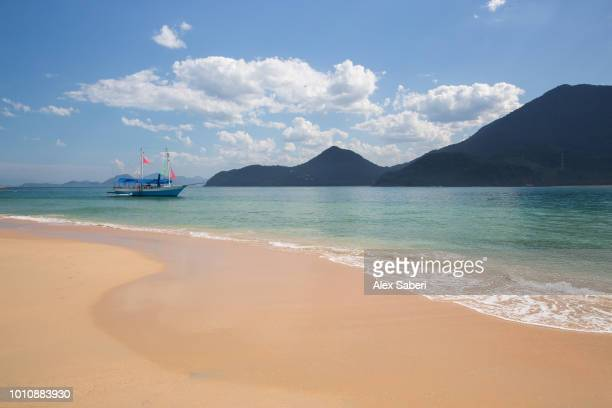 A tourist boat off the coast of a tropical beach on the Ilha do Prumirim in Ubatuba Brazil
