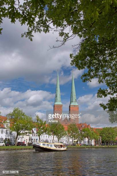 Tourist boat on the river Trave and the Lubeck Cathedral / Dom zu Lubeck / Lubecker Dom in the Hanseatic town Luebeck SchleswigHolstein Germany