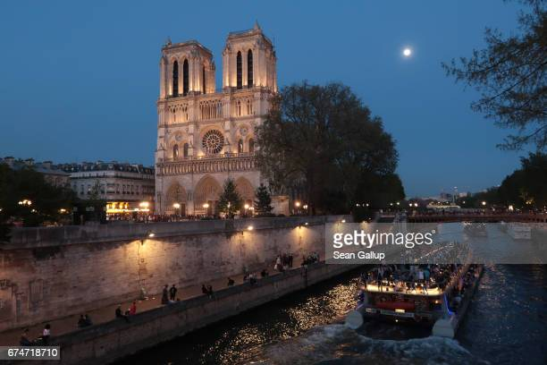 A tourist boat on the Seine River passes by Notre Dame Cathedral on April 9 2017 in Paris France Paris is among Europe's most popular tourist...