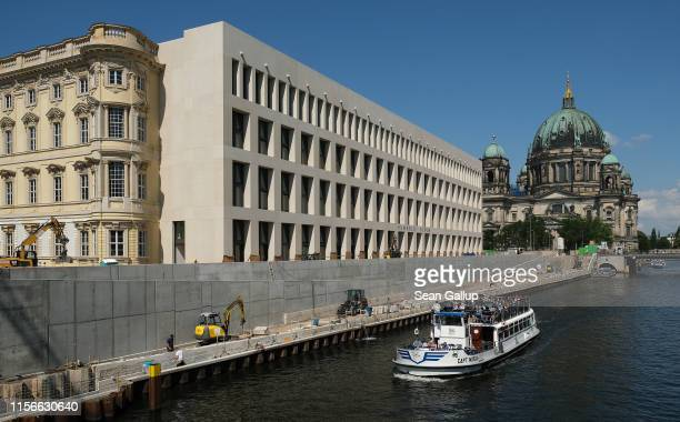 Tourist boat on the Spreee River passes by Baroque and modernist facades of the Humboldt Forum as the Dom cathedral stands behind on June 17, 2019 in...