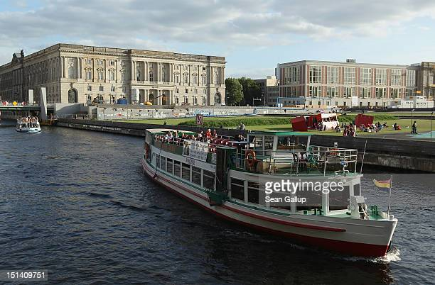 A tourist boat passes alomg the Spree river near the Neuer Marstall built in the late 19thcentury to house the horses and carriages of the Kaiser on...