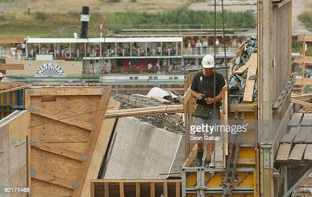 A tourist boat travels along the Elbe River behind a worker at the controversial Waldschloesschen Bridge construction site on August 4 2008 in...