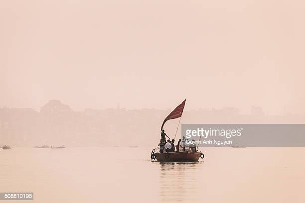 Tourist boat with flag Dawn Misty Ganges River Varanasi the oldest living city in the world one of the holiest cities across the country state Uttar...