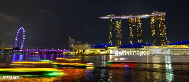 tourist boats at light speed - marina bay sands stock-fotos und bilder