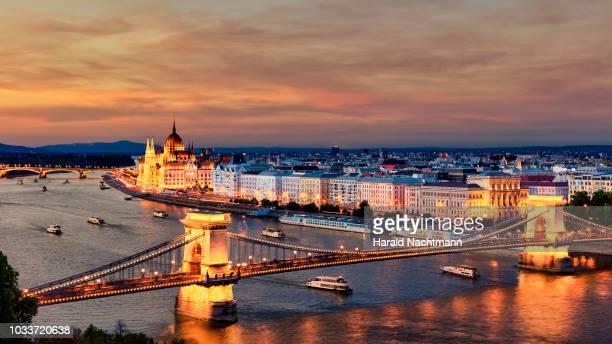 tourist boats with chain bridge and parliament building on danube river at sunset, budapest, hungary - sede do parlamento húngaro - fotografias e filmes do acervo