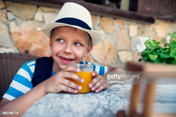 Tourist boy drinking a glass of freshly squeezed orange juice
