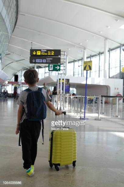 tourist boy with backpack and carrying on luggage at terminal airport - kid in airport stock pictures, royalty-free photos & images
