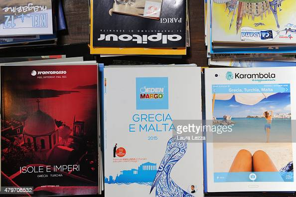 Tourist brochures for Greece are displayed inside a travel
