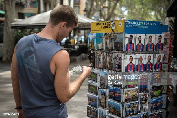 A tourist browses postcards on sale at a stall on Las Ramblas as life returns to normal following Thursday's terrorist attack on August 19 2017 in...