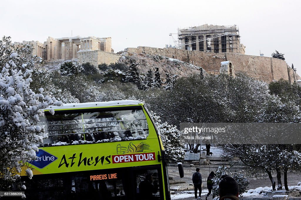 A tourist bus parks in front of the Temple of Parthenon which is covered in snow on January 10, 2017 in Athens, Greece. Schools in Athens remained closed on Tuesday and the rare snowfall caused traffic disruptions.