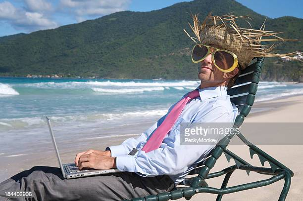 Tourist Businessman Relaxing in Beach Chair with Laptop Computer