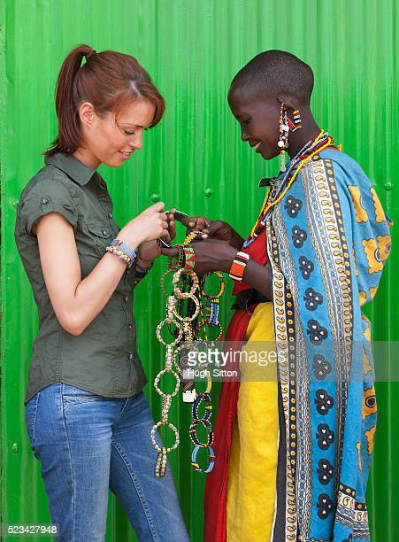 tourist buying bracelets from maasai tribeswoman. maasai mara, kenya - hugh sitton stock-fotos und bilder