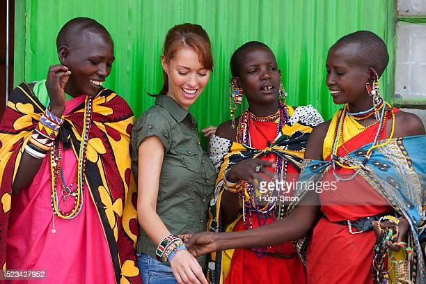 tourist buying bracelets from maasai tribeswomen, maasai mara, kenya - hugh sitton stock-fotos und bilder