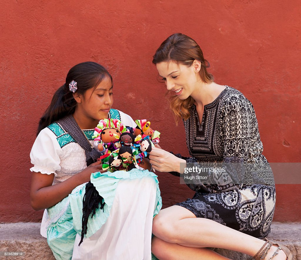 Tourist buying Mexican dolls from saleswoman : Stock Photo