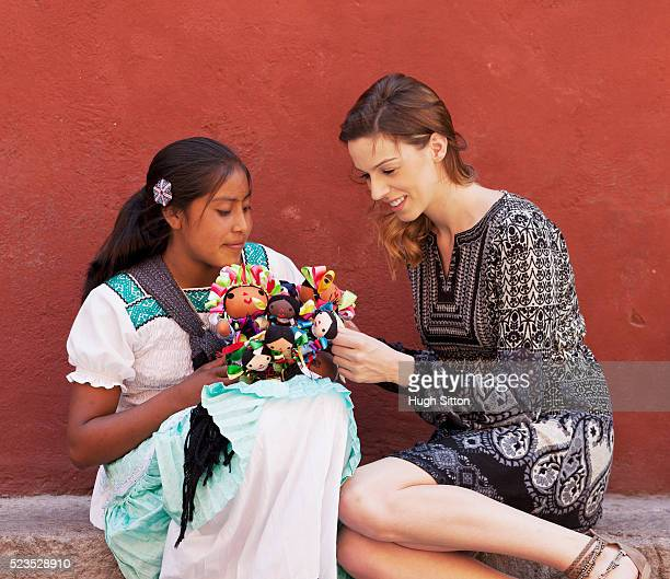 tourist buying mexican dolls from saleswoman - hugh sitton stock pictures, royalty-free photos & images