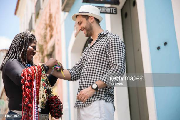 tourist buying some bonfim ribbons at pelourinho, salvador, bahia - bahia state stock pictures, royalty-free photos & images